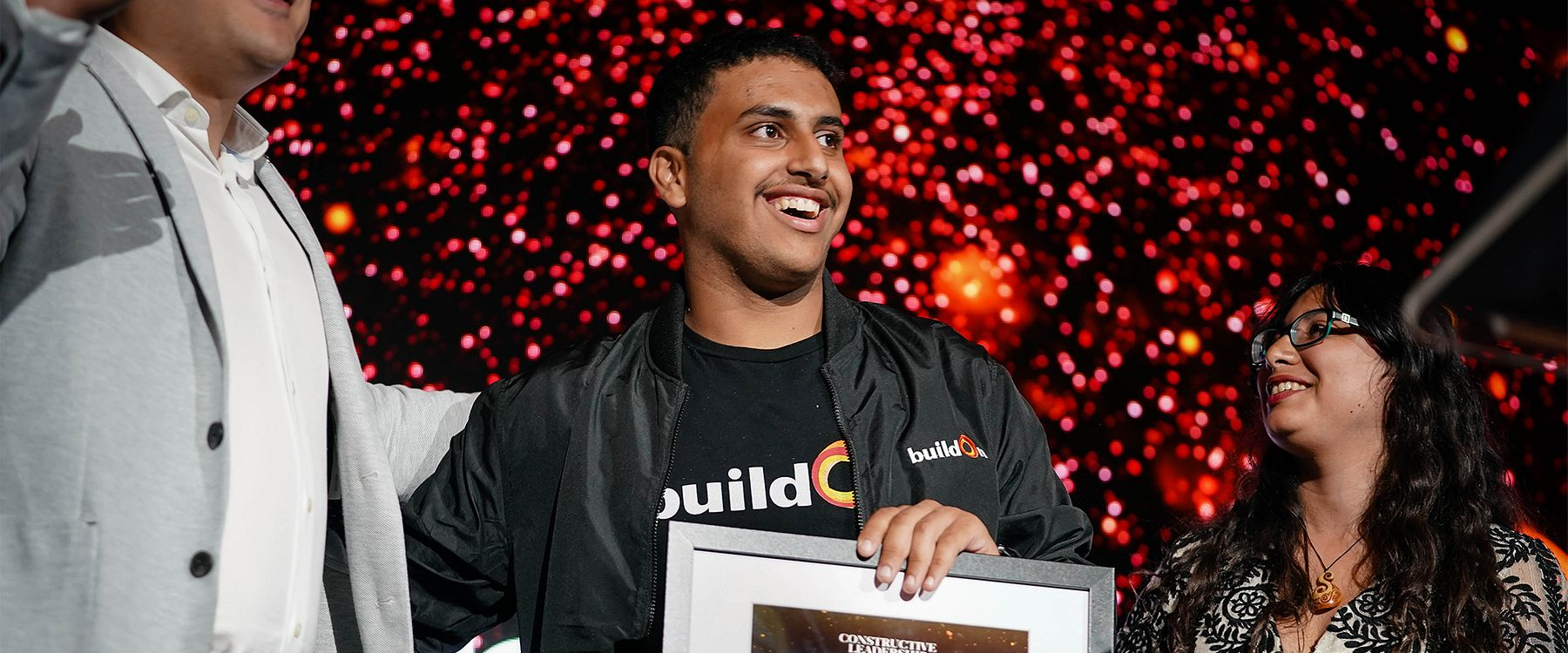 A buildOn student from Oakland stands on the stage, smiling after winning the Constructive Leadership Award.