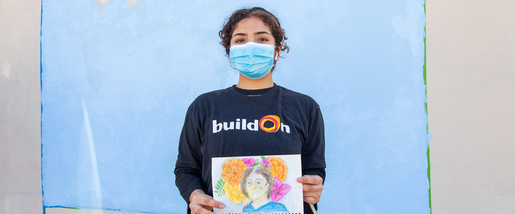 ARISE student and artist, Paulina Ramirez holding a sketch of her mural idea standing in front of a wall painted sky-blue