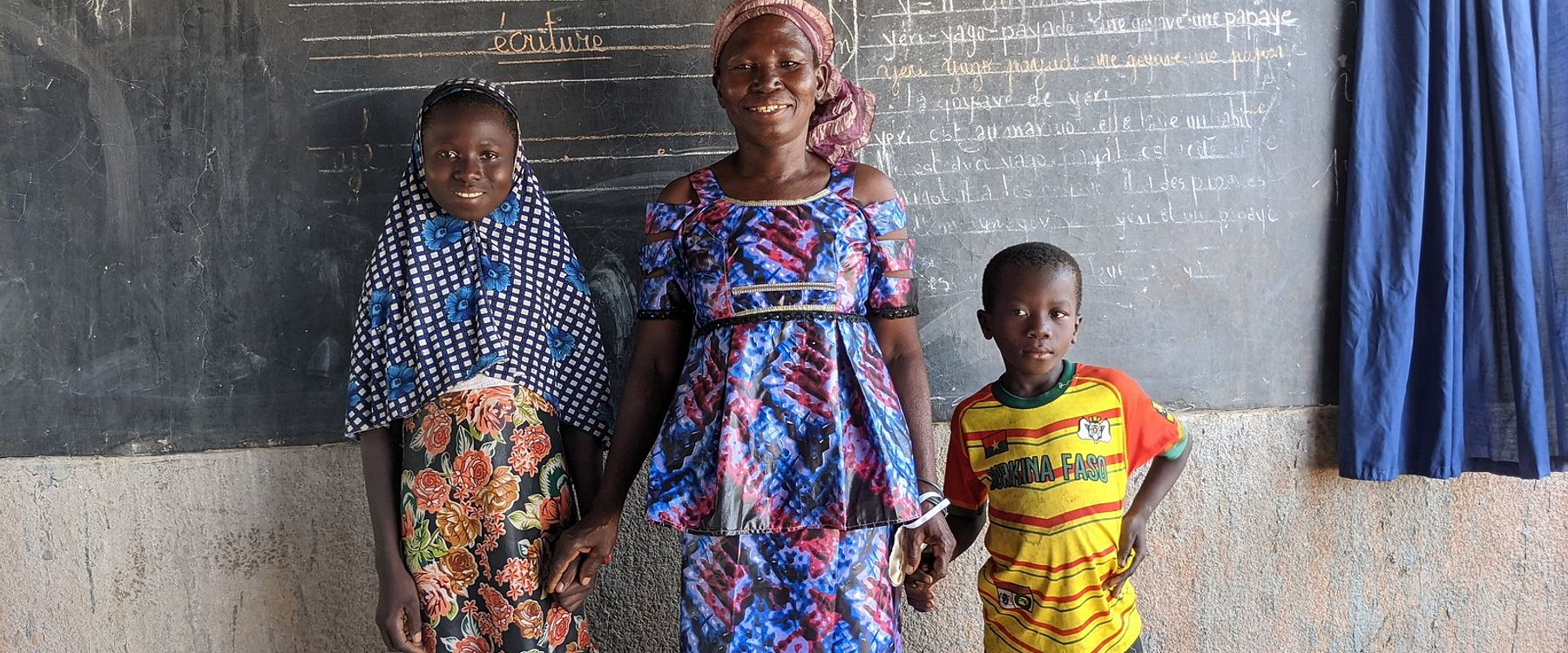 Nignan Kakoira from Sia, Burkina Faso, poses in front of classroom blackboard with her granddaughter and grandson