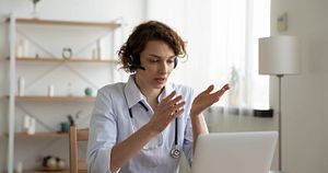 Female,General,Practitioner,Wears,White,Coat,And,Headset,Speaking,Videoconferencing