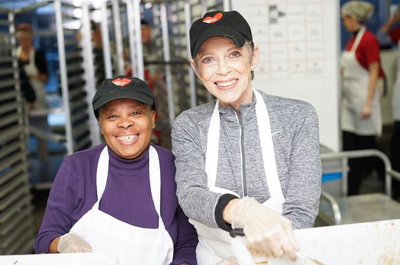 Two volunteers smiling at the camera during a meal packout