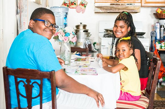 Three children sitting at a table with their meals