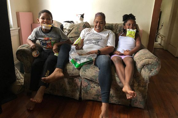 Client Asia sitting on the couch with her two grandkids. They are holding meal components
