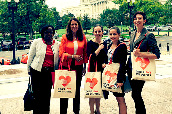 5 People holding God's Love We Deliver bags in front of the Capitol