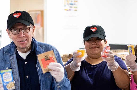 Volunteers Holding Breakfast Items