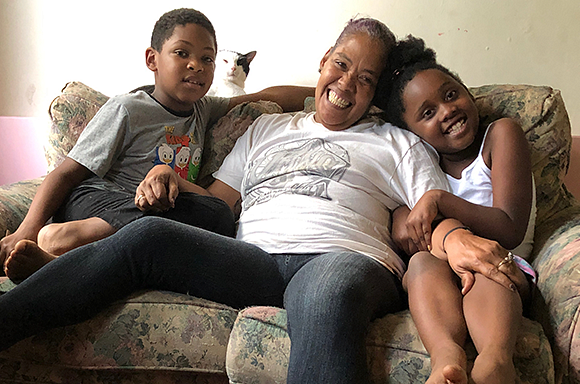 Client Asia sitting on the couch with her grandchildren and cat