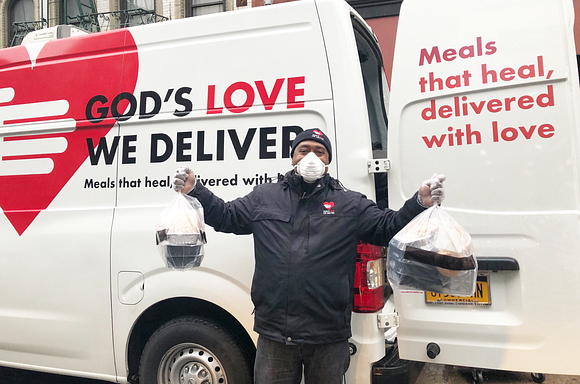 Driver Fred holding meal bags in front of a van, while he wears a mask and gloves.