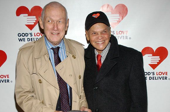 Robert Herbert and Reggie Smith smiling in front of God's Love We Deliver step and repeat