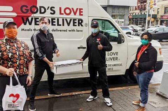 God's Love Lead Driver Kendu Outlaw holding meals with Ali Forney Center