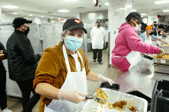 Volunteer Candy Bonder at Winter Feast packout holding a scooper