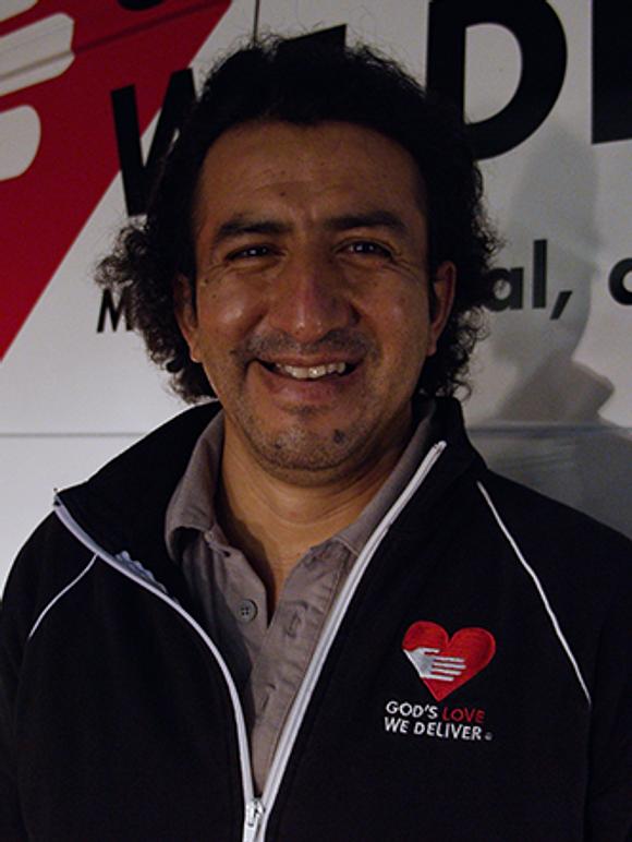 Driver Carlos Sinchi in front of a van