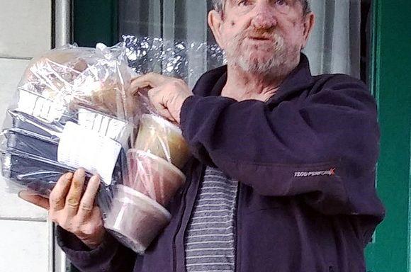 Client Robert, a veteran, standing at his door holding a bag of meals