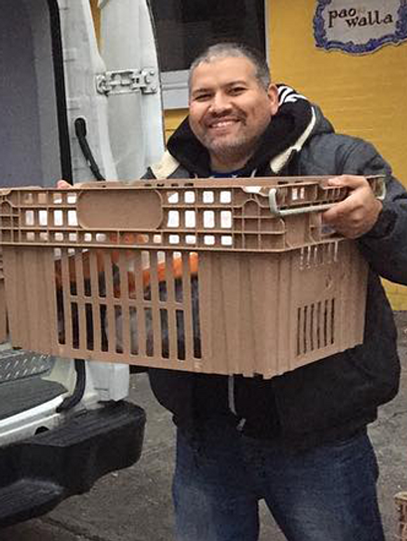 Driver Jesus Nieves holding a crate of meals while standing in front of a van