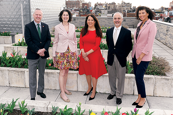 Executive Team standing on the roof smiling