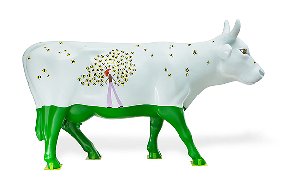 right side of the cow with top third painted white with grass green legs. The white has bumble bees and a lady with red flowing hair wearing brown long sleeved shirt and purple pants facing left in the middle with bees surround her head and body.
