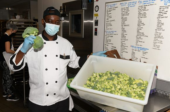 Chef Curtis in the God's Love kitchen holding up heads of broccoli.
