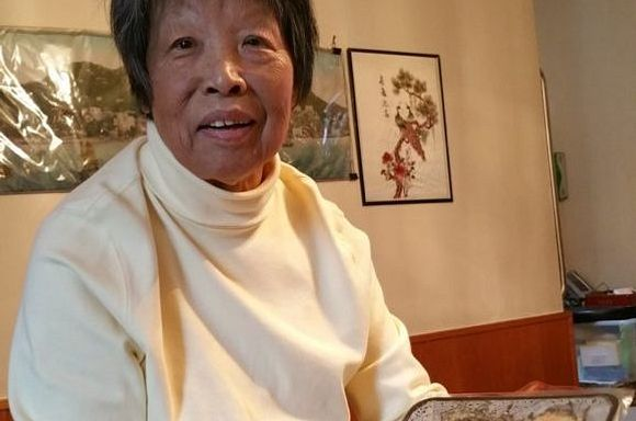 A photo of client, Ying, in her kitchen holding a meal she received from God's Love.