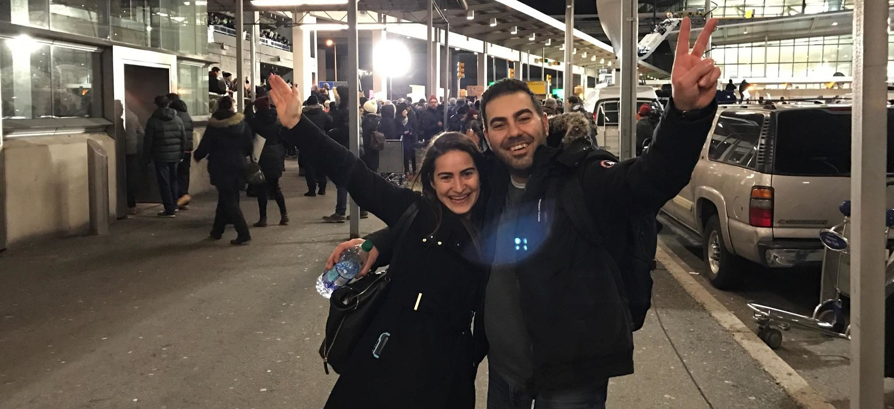 A woman and a man stand outside an airport with their arms raised in celebration. They both wear winter coats.