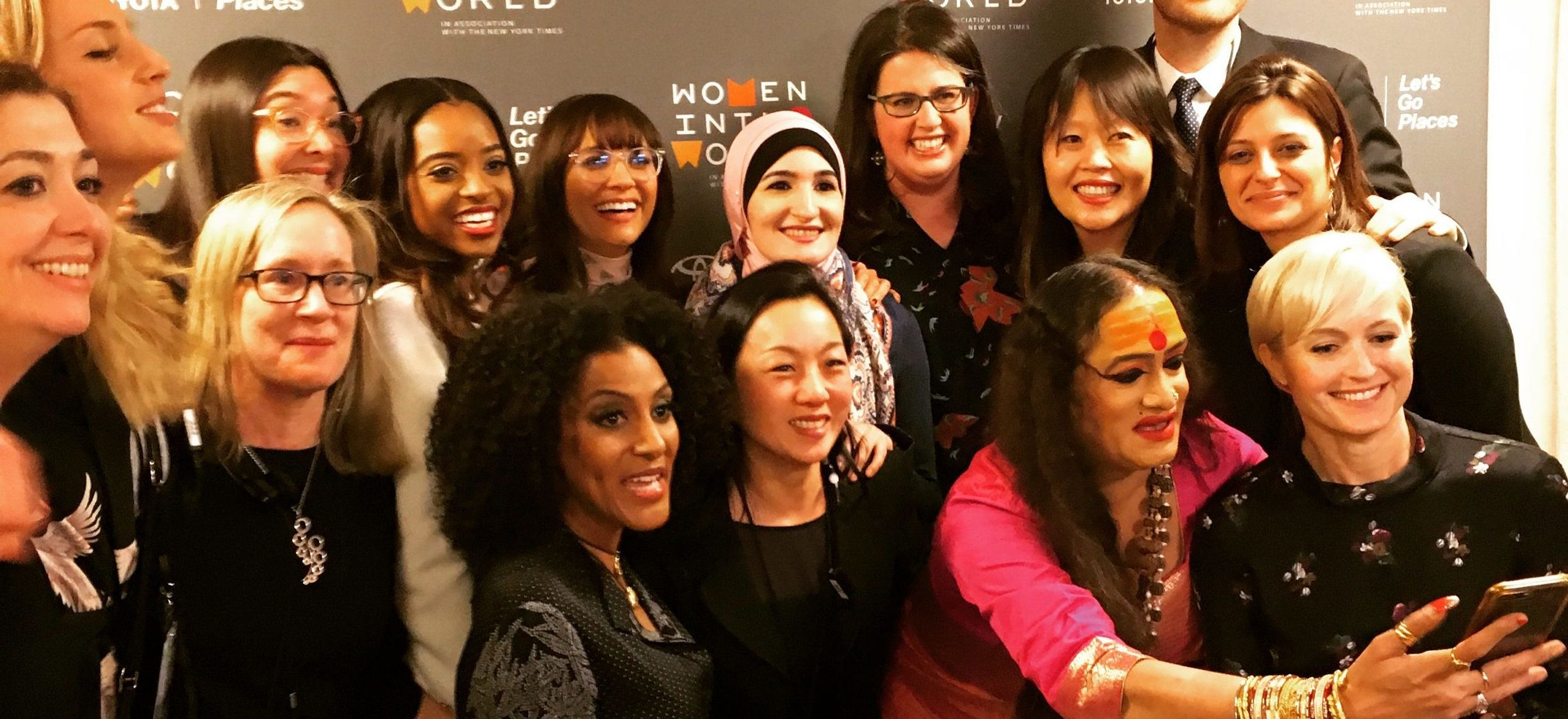 A group of 14 women (including IRAP Executive Director Becca Heller) and 1 man huddle together for a selfie in front of a Women in the World-branded popup banner.