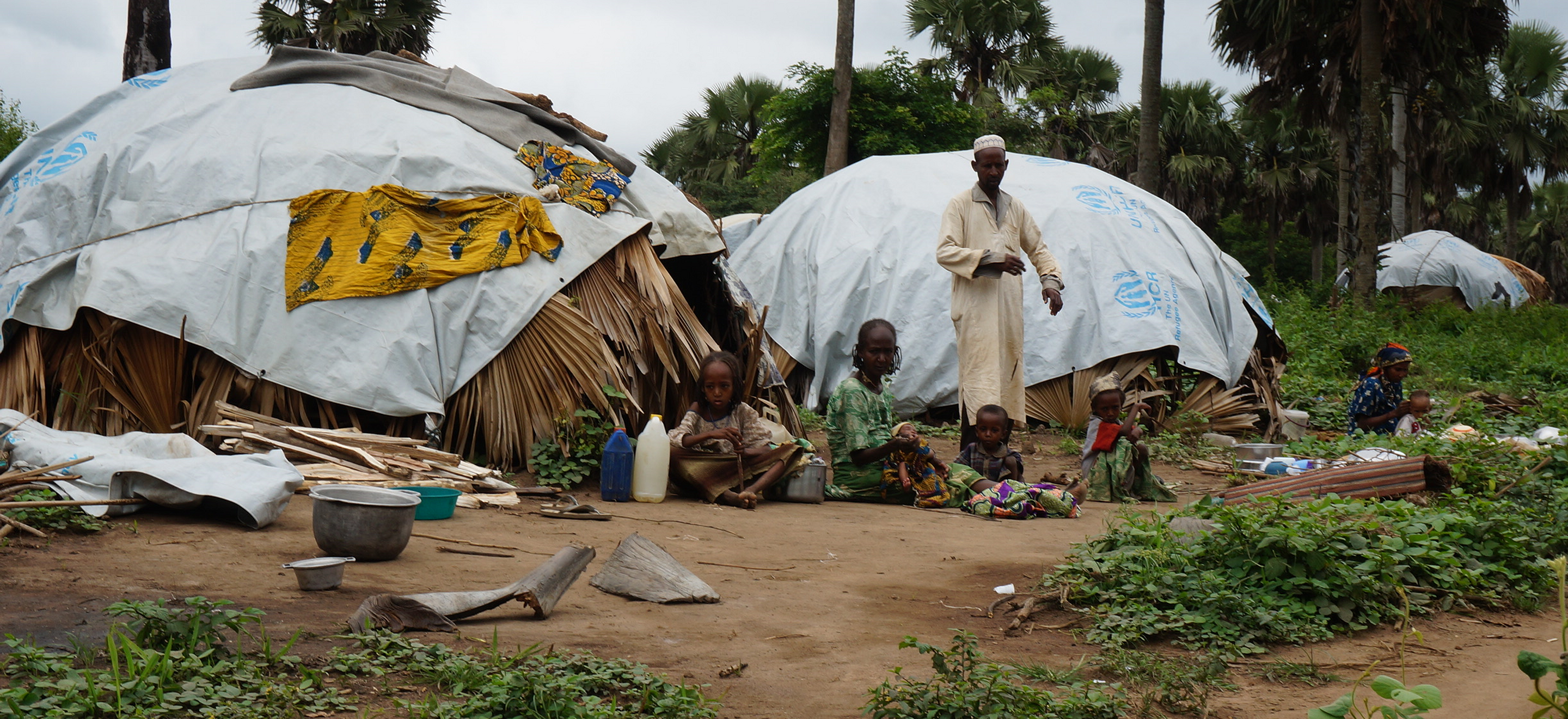 A group of six adults and children sit on the ground doing various tasks. Palm trees and tents are visible.