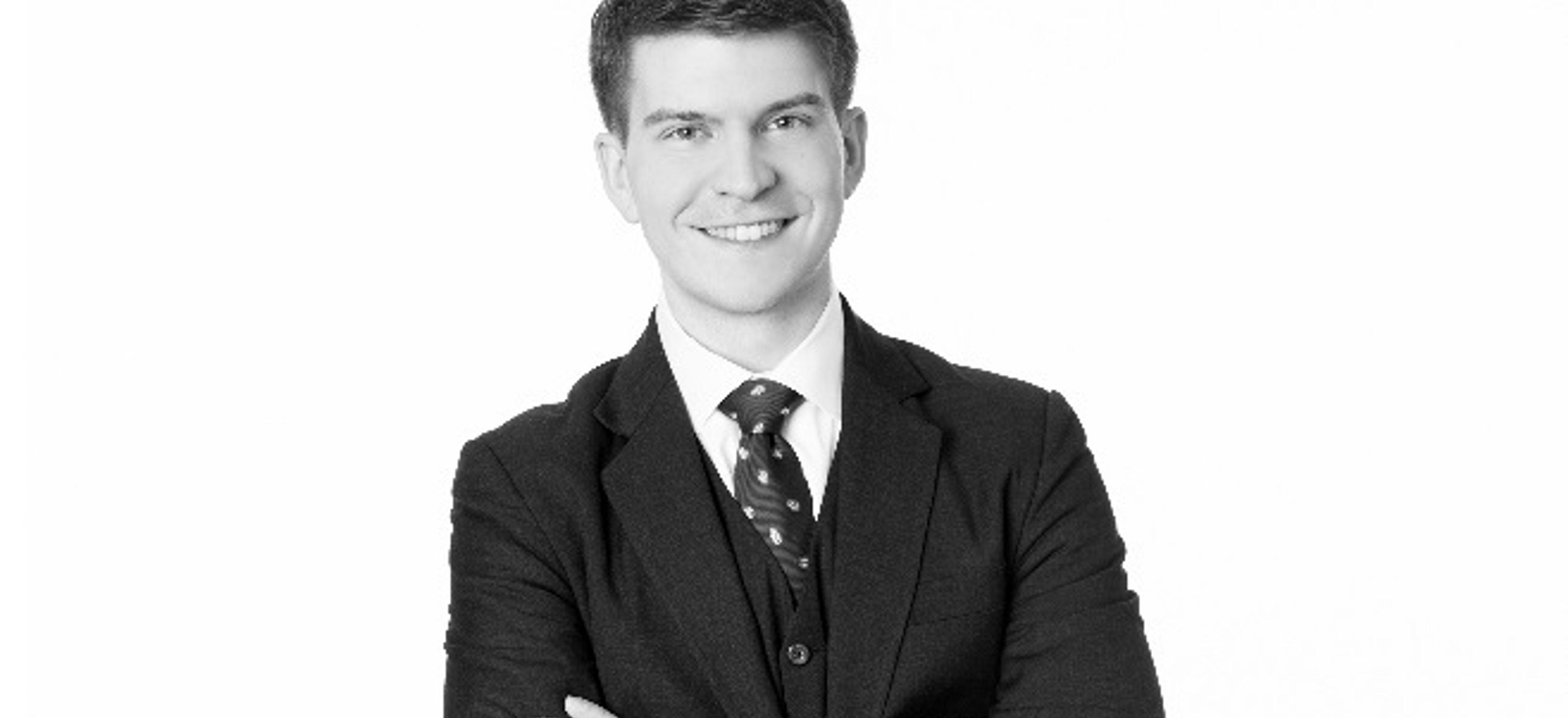 A black and white headshot of IRAP alumnus Jay Minga. He wears a three piece suit and his arms are folded in front of his body.