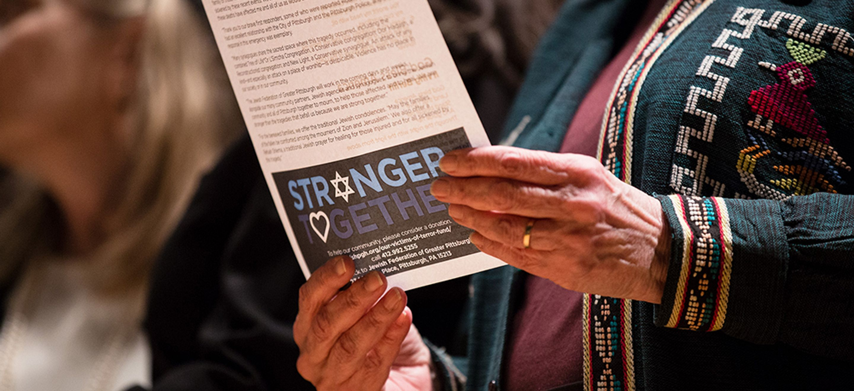 """A woman wearing an embroidered jacket holds a program for the National Refugee Shabbat with the words Stronger Together visible. The """"o"""" in stronger is a Star of David and the """"o"""" in together is a heart."""