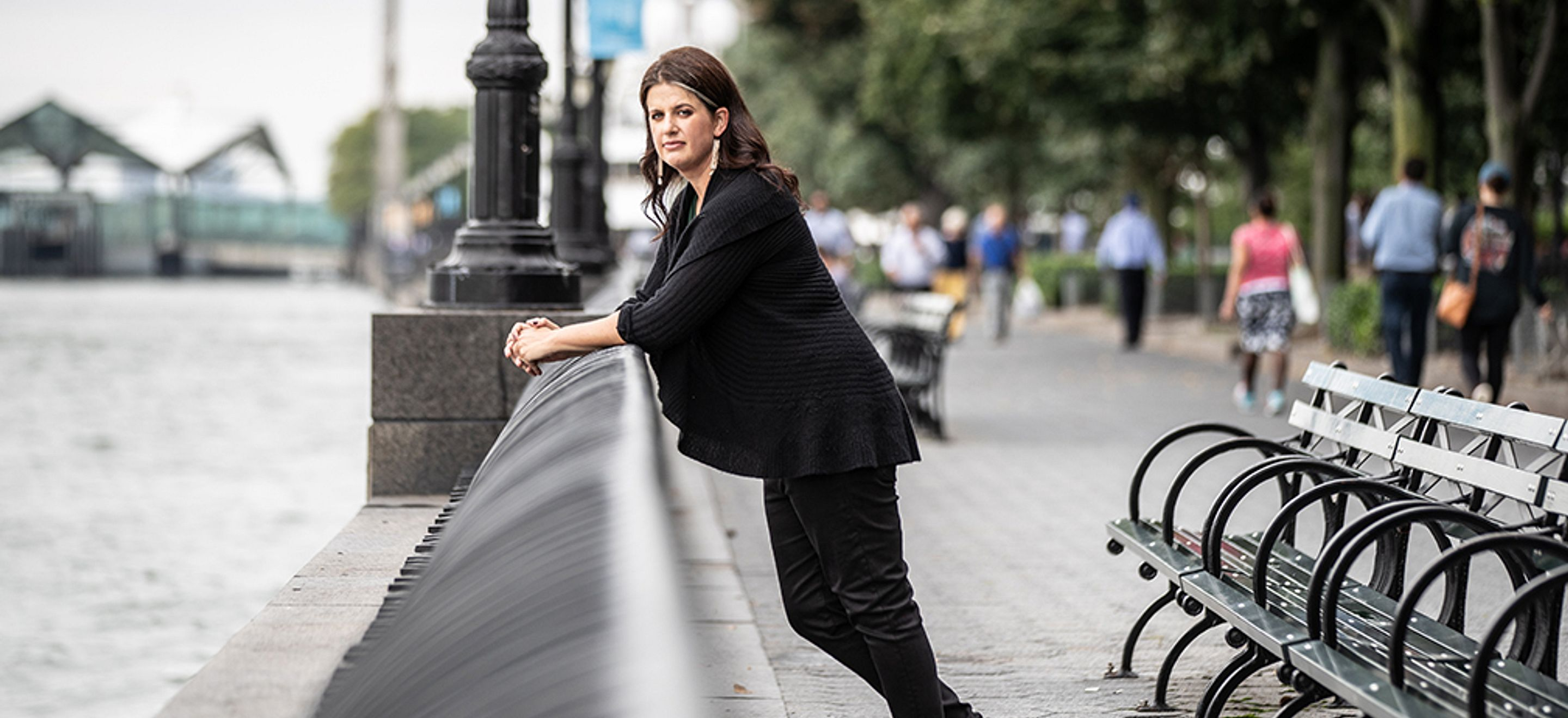 IRAP Executive Director Becca Heller leans against a railing in Battery Park. She wears black jeans, a sweater, and sneakers.