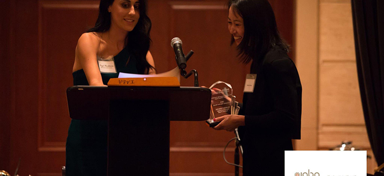 A woman at a podium hands IRAP Litigation Director Mariko Hirose a glass Community Service Award at an Iranian American Bar Association event.