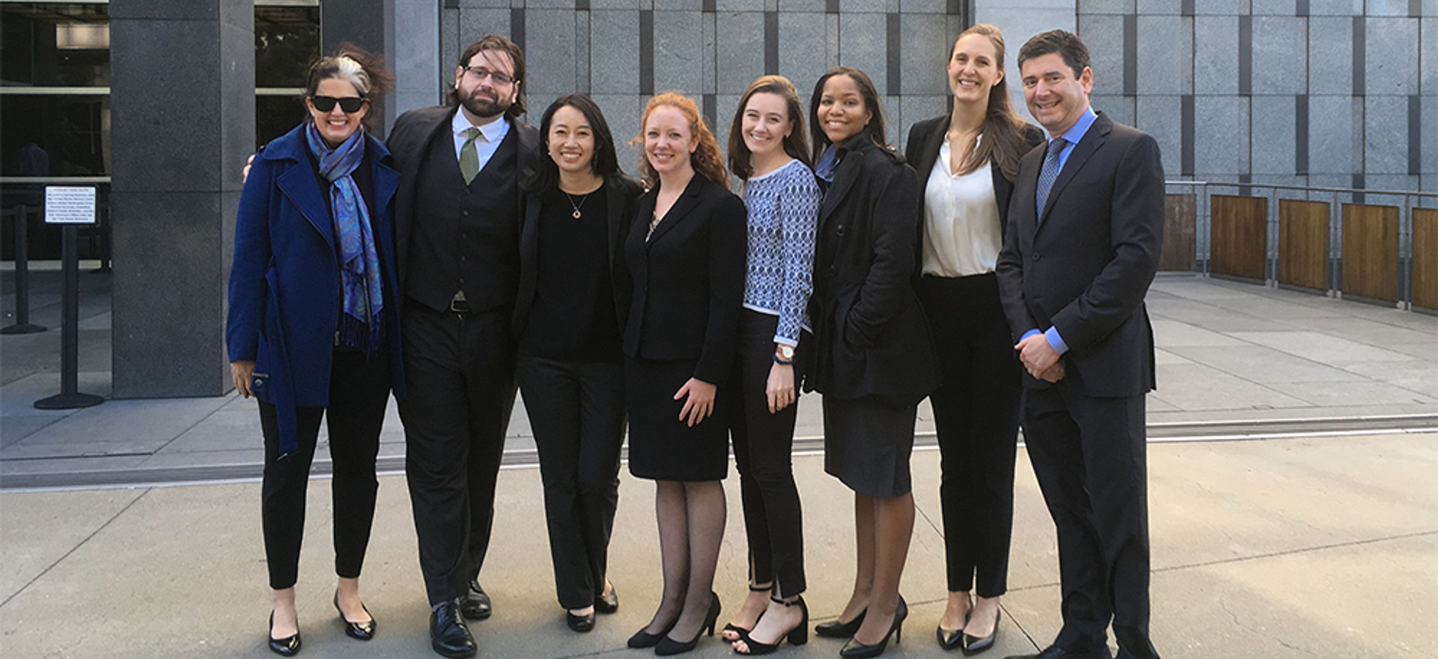 A group of eight people - some IRAP staff, some pro bono partners - dressed in professional attire outside a courtyard.