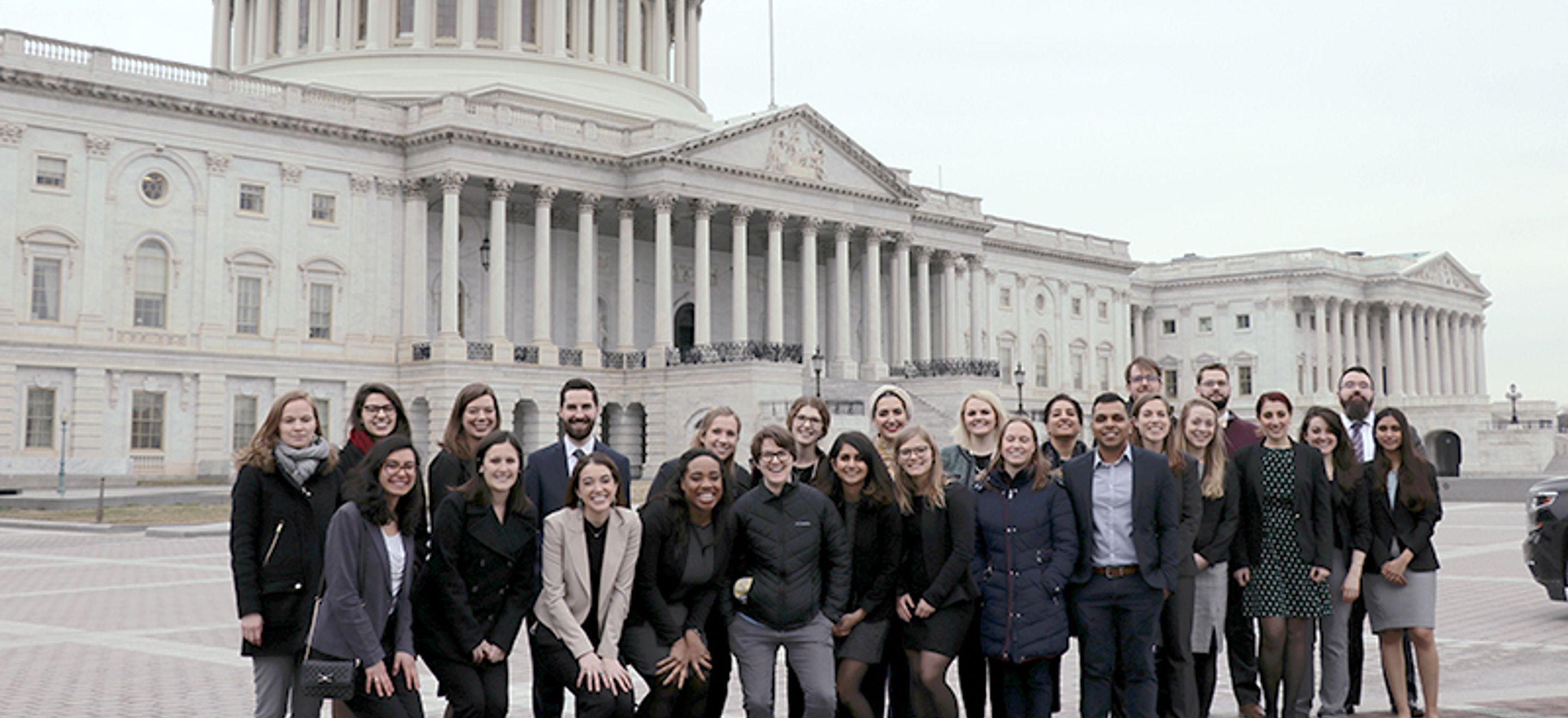 A group of 26 people - IRAP staff and law students stand in front of the U.S. Capitol building.