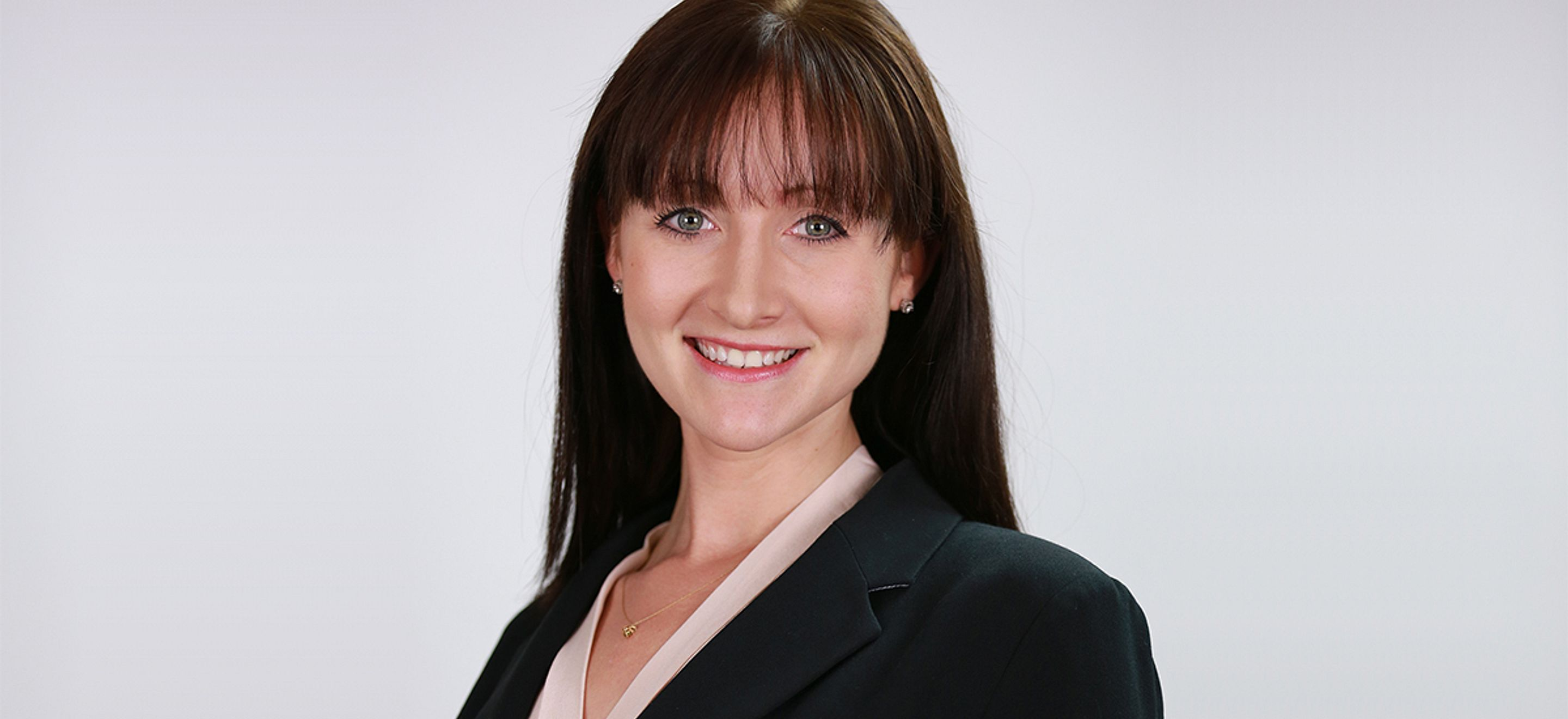 A headshot of IRAP alumna Yekaterina Reyzis. She has straight dark brown hair with bangs and smiles into the camera. She is wearing a light pink blouse with a black blazer and stands against a white background.