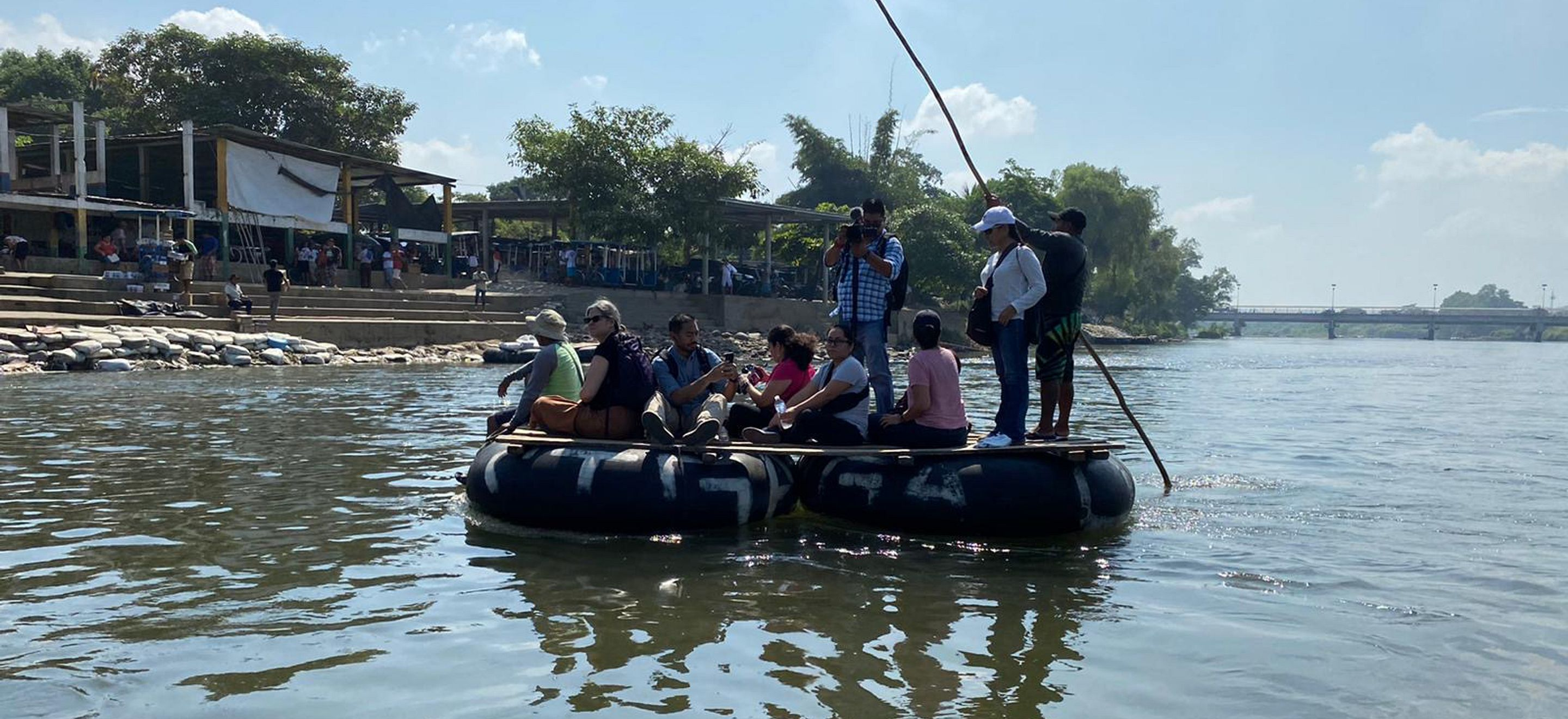 Members of a fact-finding delegation cross a river that divides Mexico from Guatemala. 6 members of the delegation are seated across two black inner tubes connected by a wooden slab. 3 members of the delegation stand on the raft, one with a video camera, one with a stick to steer the raft. A bridge is visible in the distance, and on the shore there are concrete stairs and many people congregated under open pavilions.