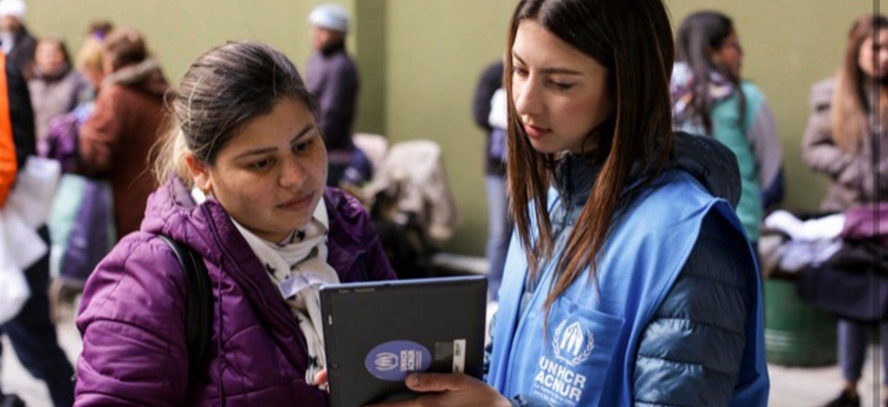 An IRAP Law School Chapter alumna wears a UNHCR vest and holds a tablet as she meets with a displaced woman wearing a purple winter jacket.