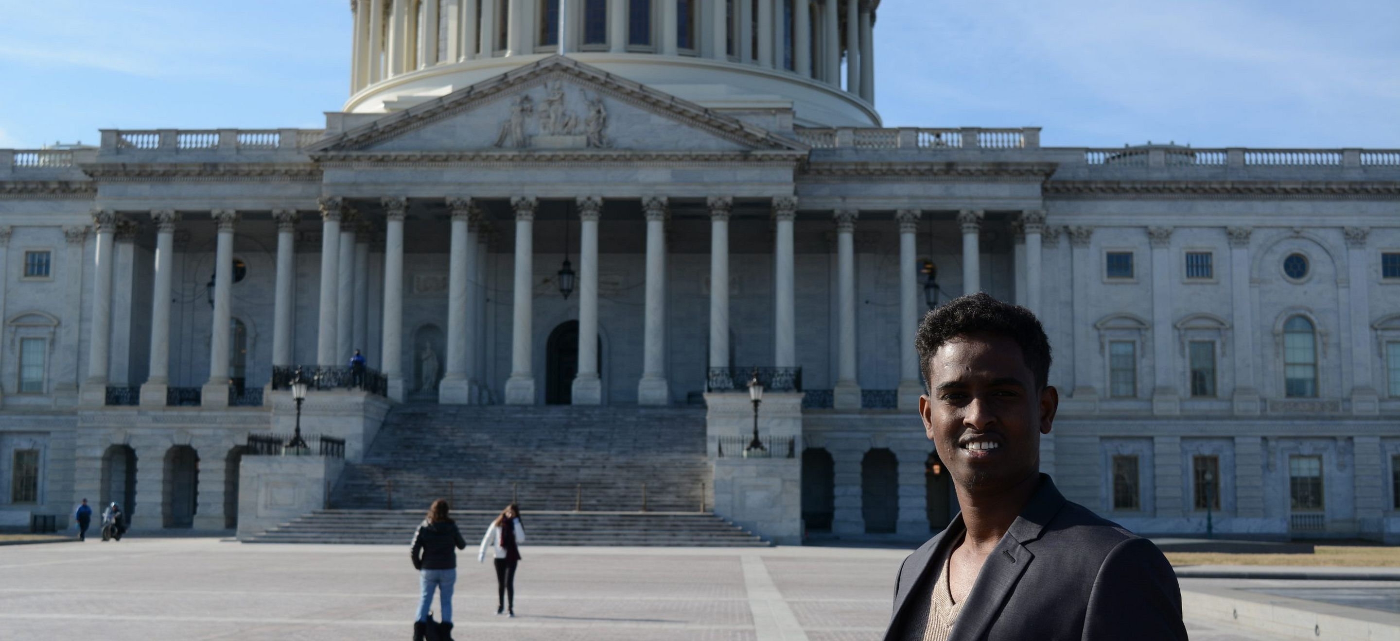A young Somali man in a black suit jacket poses in front of the U.S. Capitol.