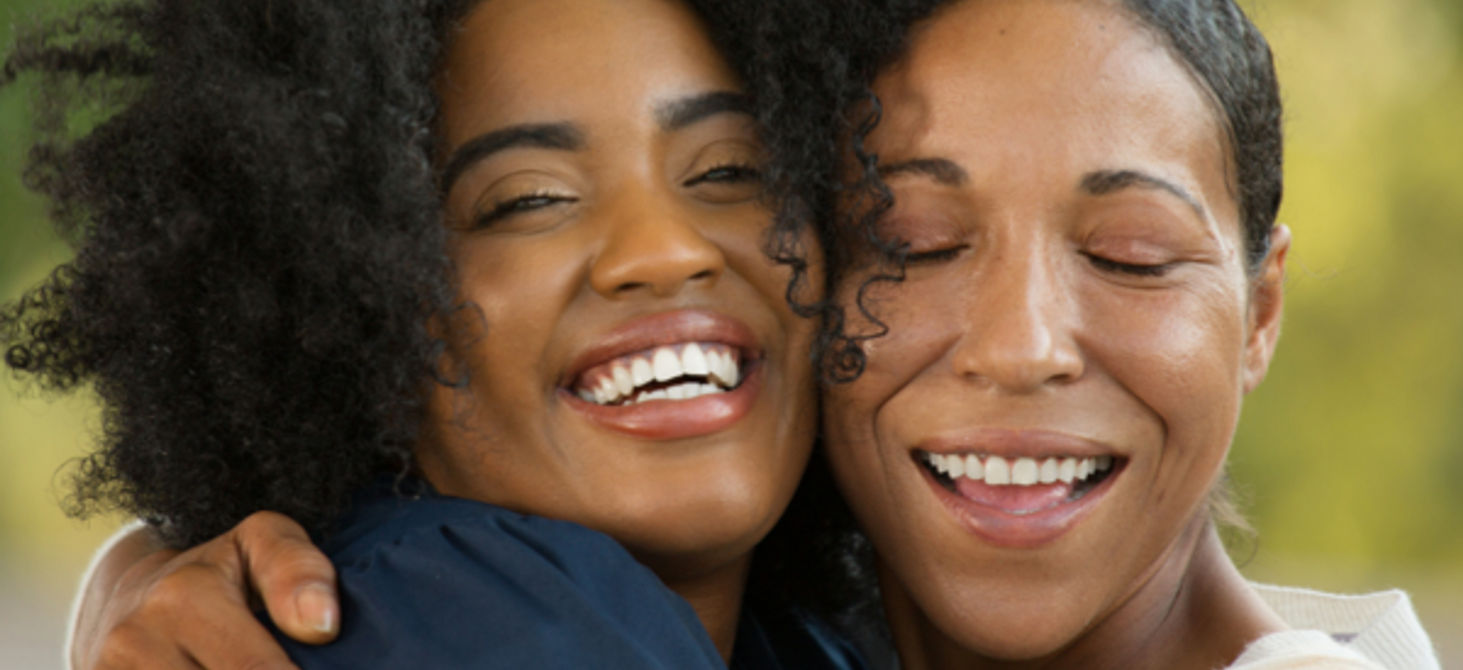 Two Black women embrace cheek to cheek. They both smile. The woman on the left looks slightly past the camera, the woman on the right has her eyes closed.