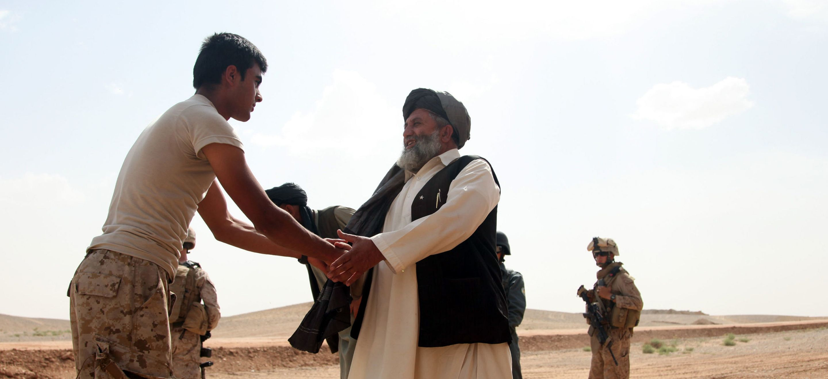 An Afghan interpreter shakes the hand of a local Afghan elected official. The official wears a white collared tunic with black vest and a turban, he has a bushy grey beard. The interpreter has short black hair and wears a t-shirt and camouflage pants. There are U.S. soldiers in the background.