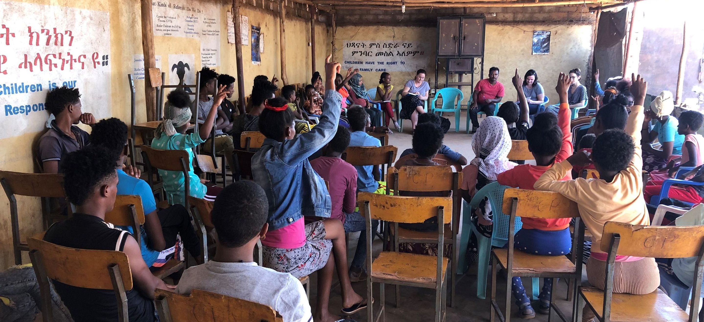 Members of IRAP and UNHCR staff meet with unaccompanied refugee children in a classroom in a northern Ethiopian refugee camp. The children sit in rows of chairs facing the staff. Several of them have their hands raised.