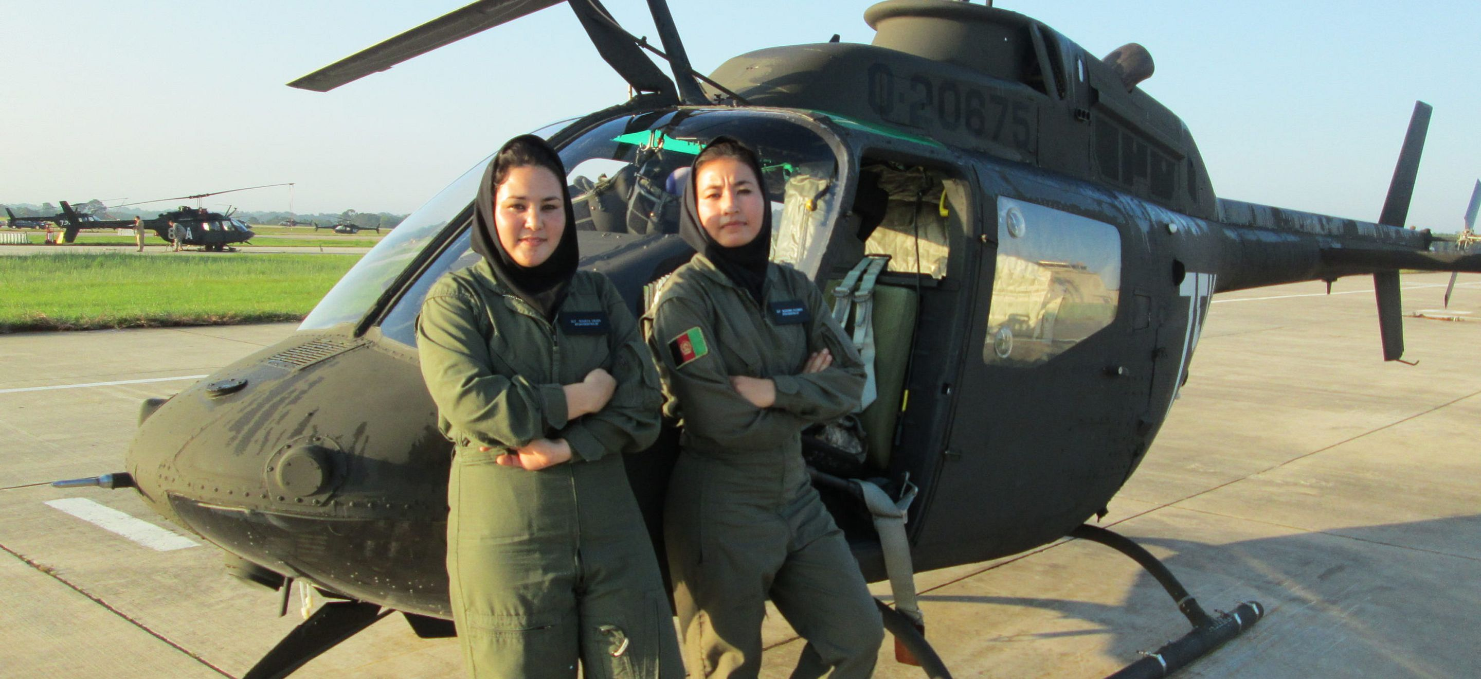 Two Afghan women pose, arms folded, in front of a military helicopter on a tarmac. They wear olive green pilot uniforms with black head scarfs.