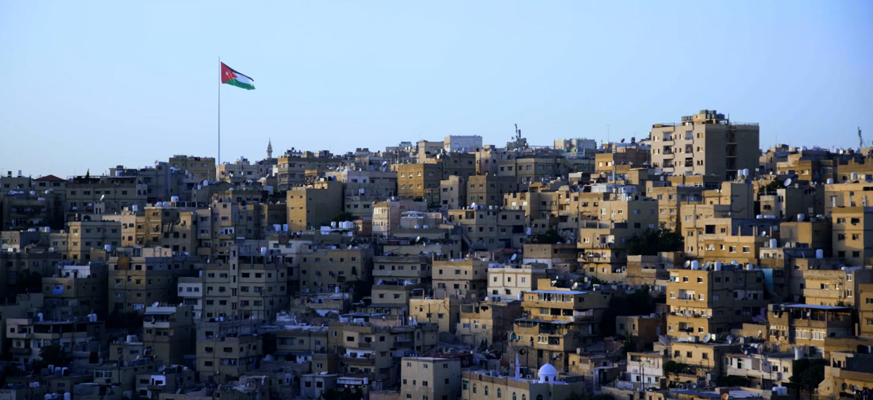 Tan buildings built into a hillside form the Amman cityscape. In the distance, there is a Jordanian flag and a minaret.