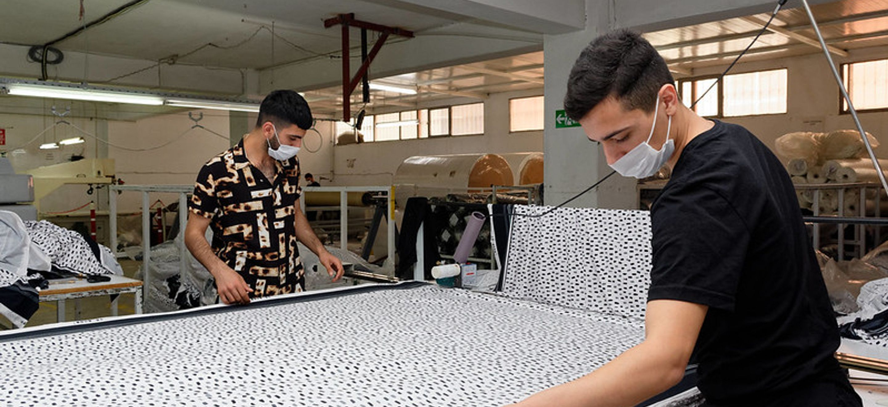 Two young men work in a garment business. They are wearing medical mask and are working with a large piece of printed fabric.