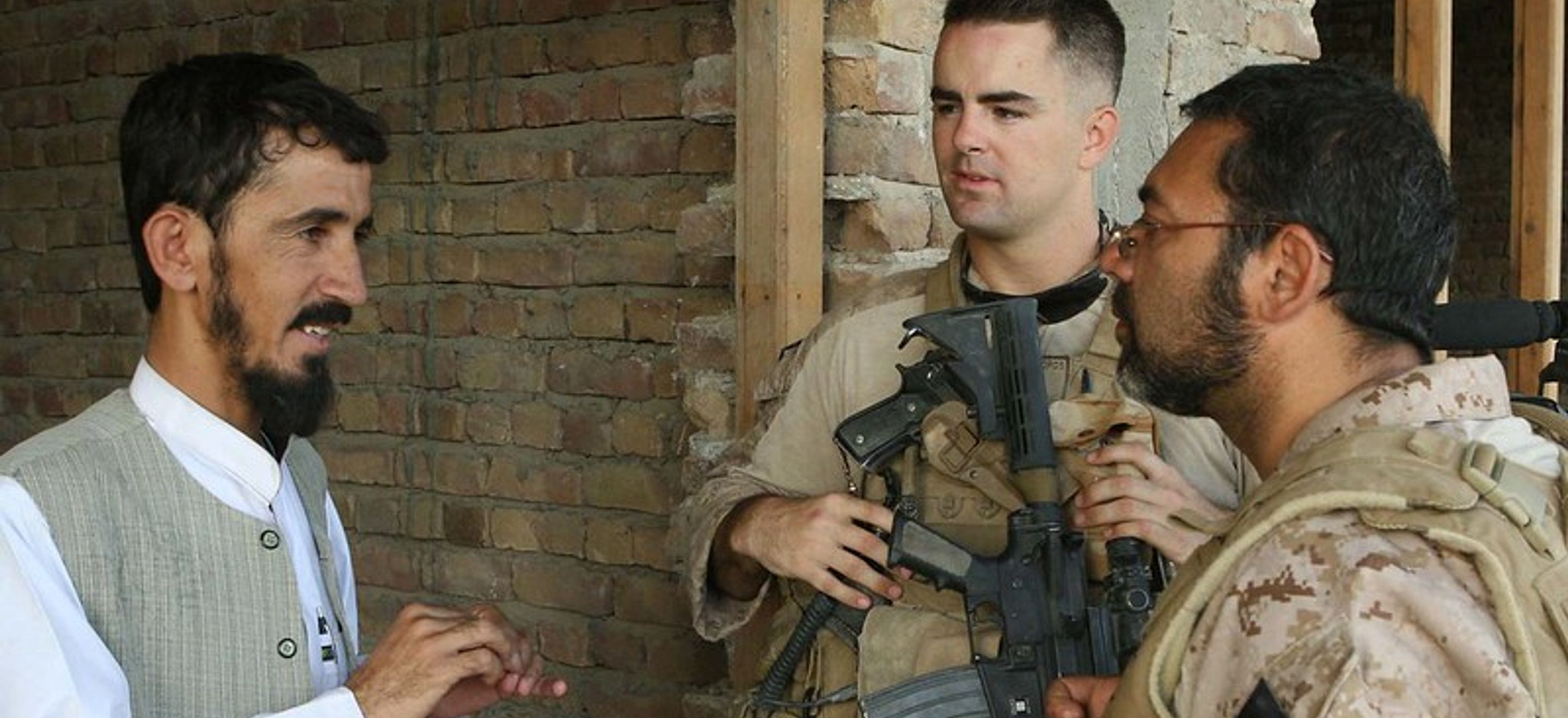 An Afghan interpreter and a U.S. soldier, both dressed in desert fatigues, talk to an Afghan man with a beard and mustache, who wears a white shirt with a banded collar and a light grey vest. The U.S. soldier carries multiple weapons, and the interpreter wears glasses and a protective vest. They are standing in front of a brick building.