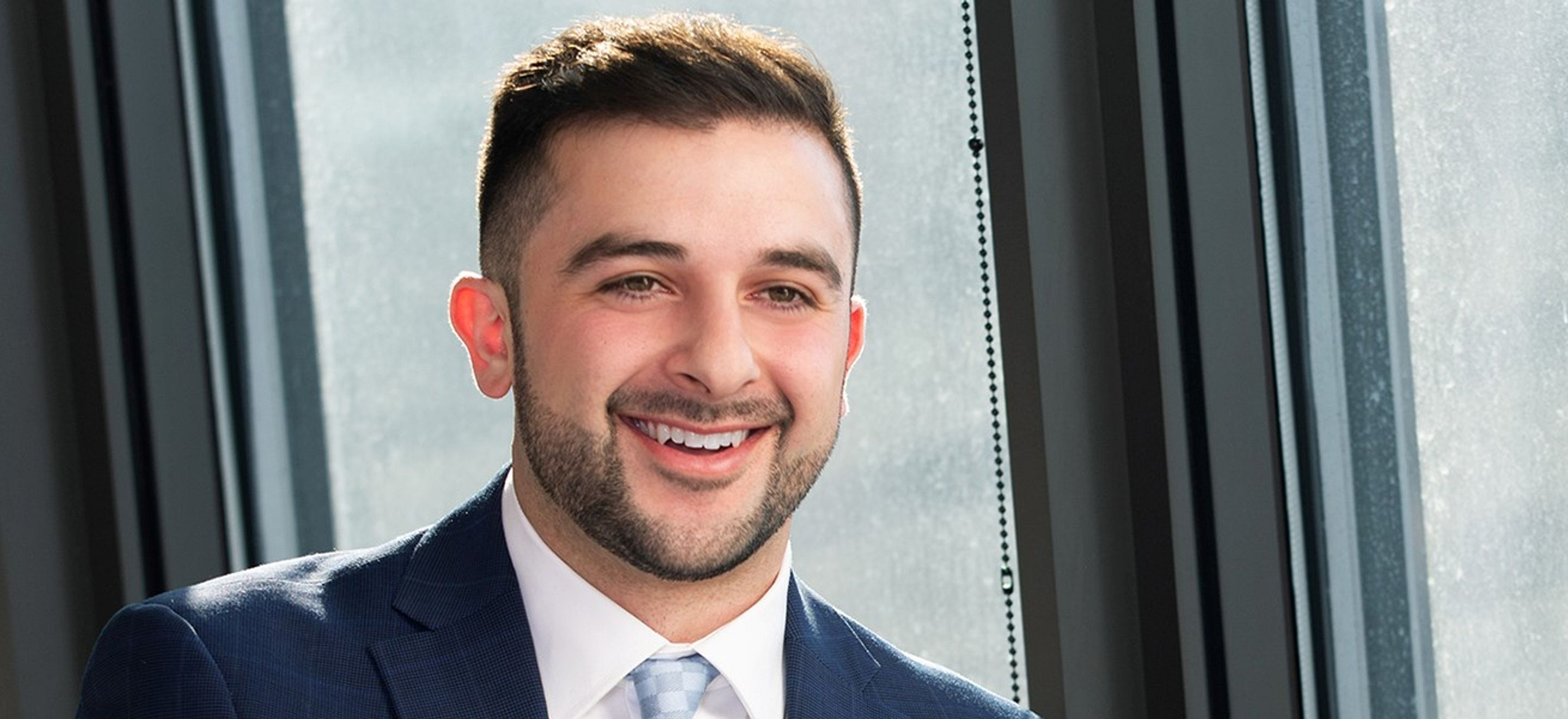 Beneel Babaei, an alumnus of an IRAP Law School Chapter, smiles, looking slightly past the camera. He wears a blue suit and has brown hair, brown eyes, and short facial hair. He poses against unobstructed windows in an office setting.