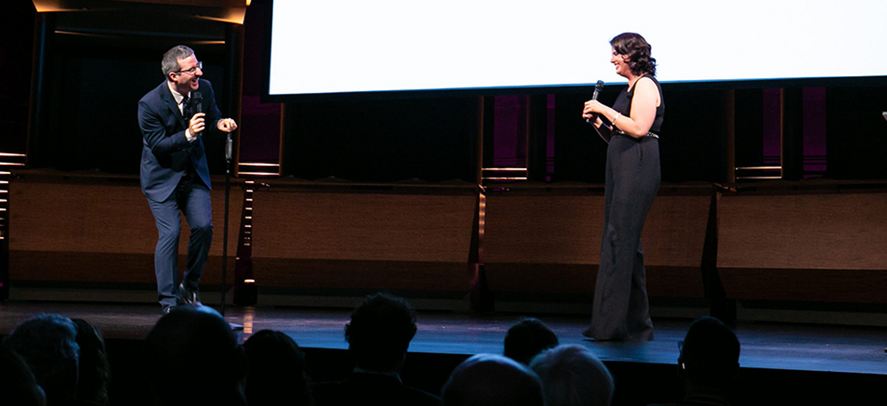 Comedian John Oliver and IRAP Executive Director Becca Heller stand onstage at a benefit. The heads of audience members are barely visible, the stage has a slight blue wash, and there is a lucite podium with a purple sign with the IRAP logo.