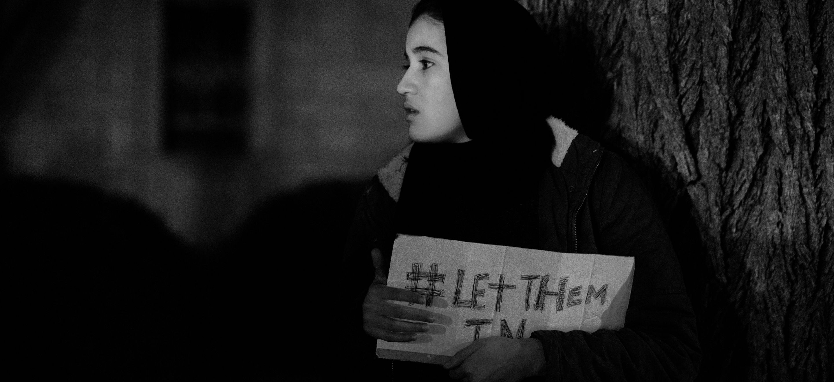 A young woman wears a black head scarf and a winter jacket. She holds a cardboard sign reading #LetThemIn close to her body.