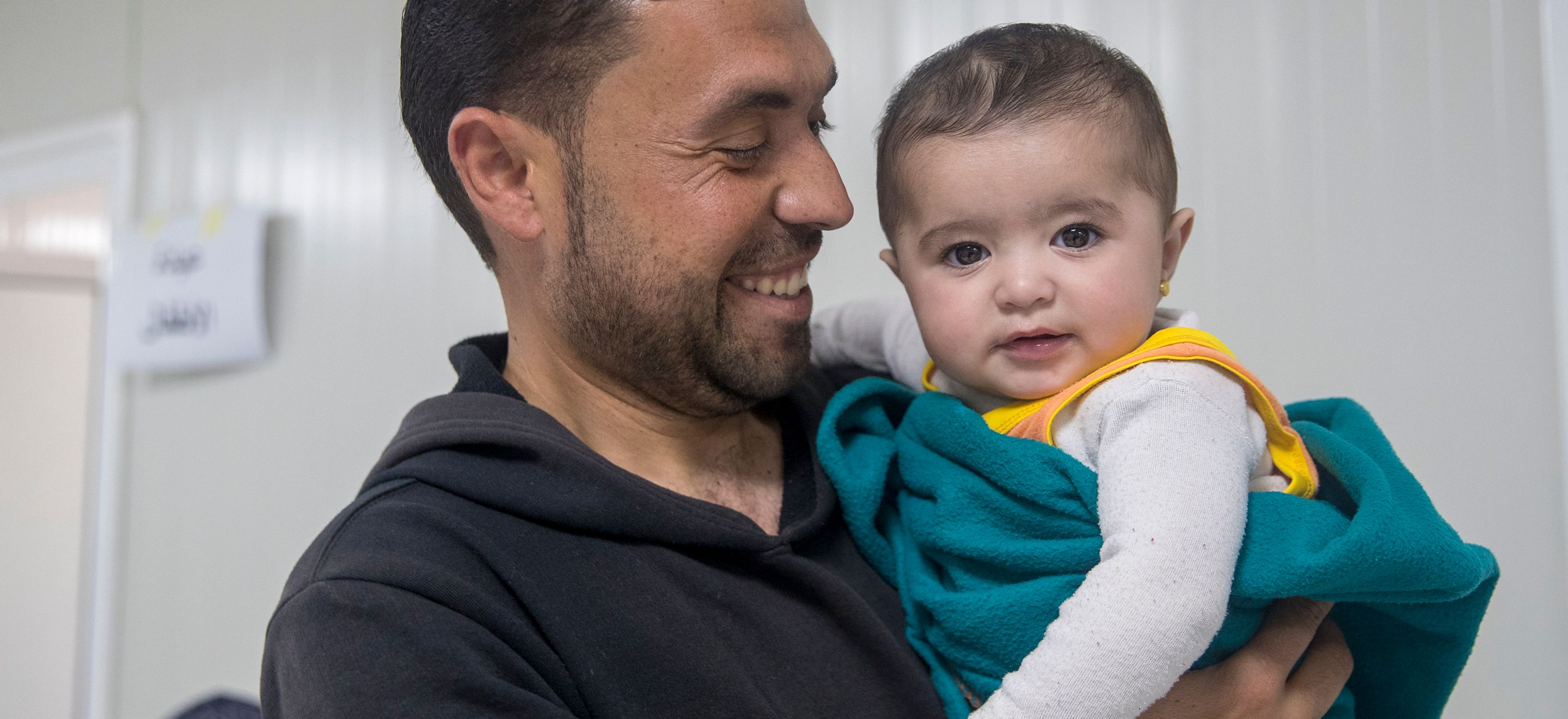 A Syrian father holds his infant daughter in the waiting area of a medical clinic in a Jordanian refugee camp. The father wears a black hooded sweatshirt and the child wears a long sleeve white shirt and is wrapped in a teal fleece blanket.
