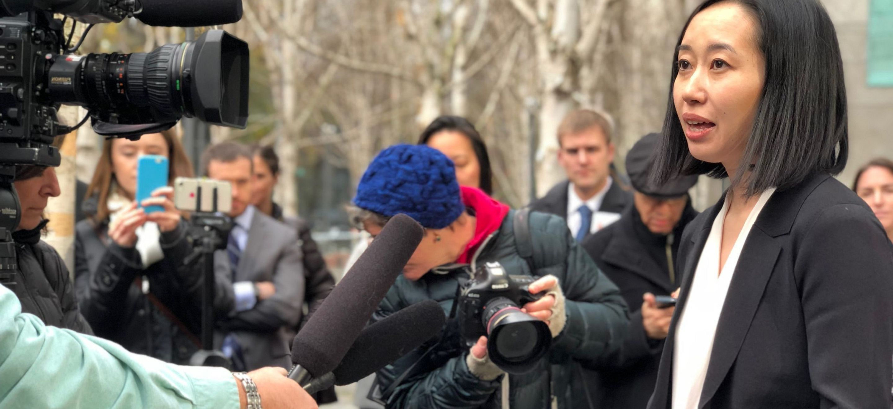 Mariko Hirose, IRAP Litigation Director, addresses journalists at an outdoor press conference. She is surrounded by several journalists with cameras, microphones and notepads. She has straight, shoulder length black hair and wears a white blouse and black blazer.