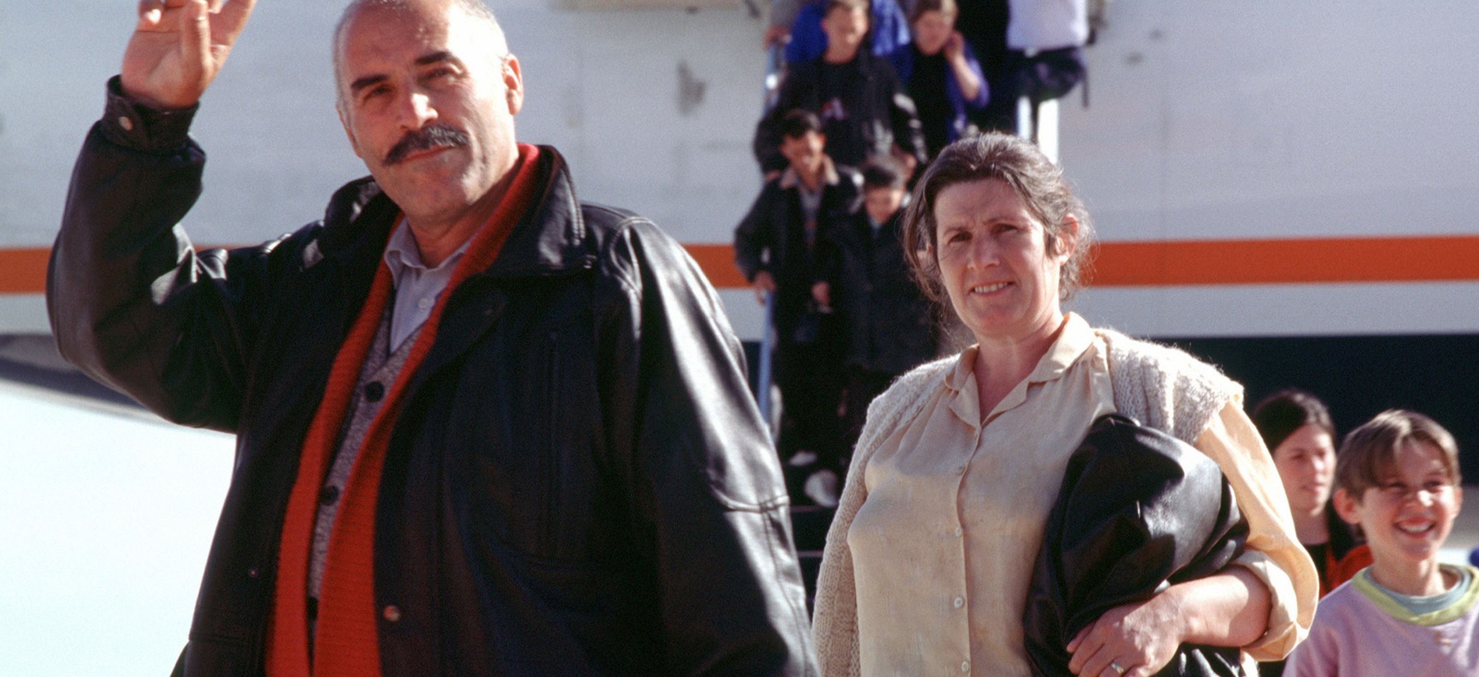Kosovar refugees arriving in the United States. In the background, a plane is partially visible, with several of the refugees - many of them children - descending a metal staircase onto the tarmac. In the foreground, are a man and a woman from Kosovo. The man has olive colored skin and holds up a peace sign. He is almost bald, with some short white hair visible. He has a full mustache and dark brown eyebrows. He wears a leather jacket with a red wool sweater underneath. A woman with fair white skin and brown hair pulled back wears a beige blouse with a beige wool sweater and holds a brown leather jacket in her left hand.