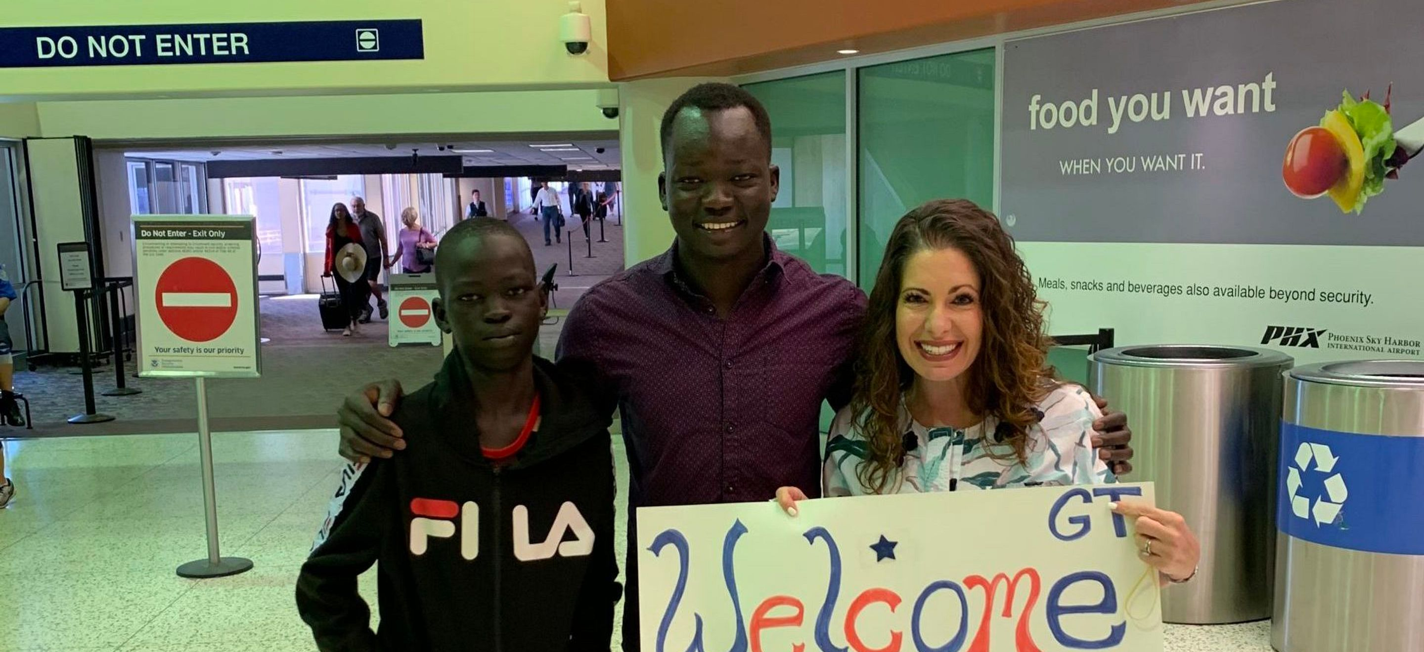 "A teenage boy and a young man with deep black skin and closely cropped black hair (brothers who have just been reunited after years separated by harsh immigration policies) stand with a white woman with wavy, shoulder-length brown hair in an airport arrivals corridor. The woman is holding a hand-written poster that says ""Welcome"" with an American flag. The young man and the woman have big smiles on their faces, and the teenage boy has a stoic look on his face. The teenage boy is wearing a black zip-up FILA hoodie, the young man wears a plum colored button-down shirt, and the woman wears a white blouse with teal and gray swirly patterns on it."