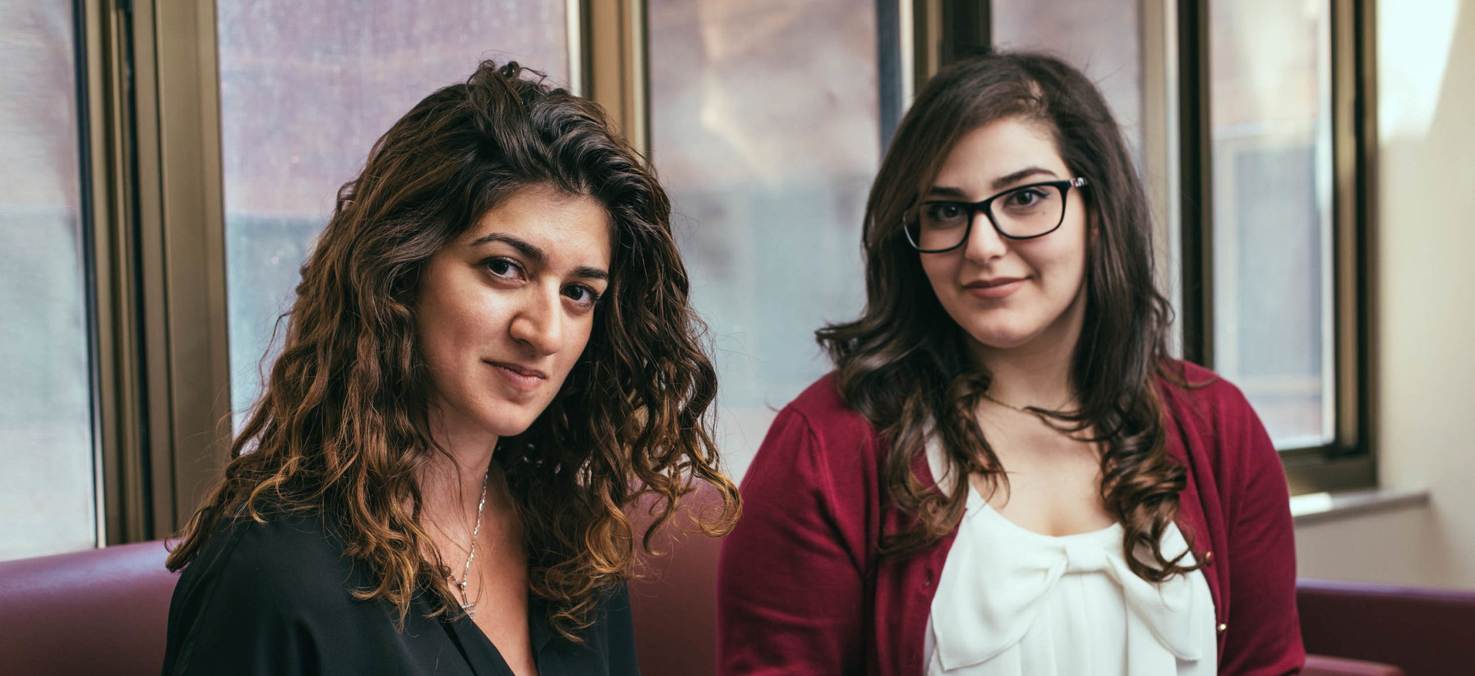Two young women look into the camera. The woman on the left has shoulder length wavy brown hair and light brown skin. The woman on the right has pale skin and long brown hair that curls slightly at the bottom. She wears glasses. Both women are seated on a maroon colored couch.