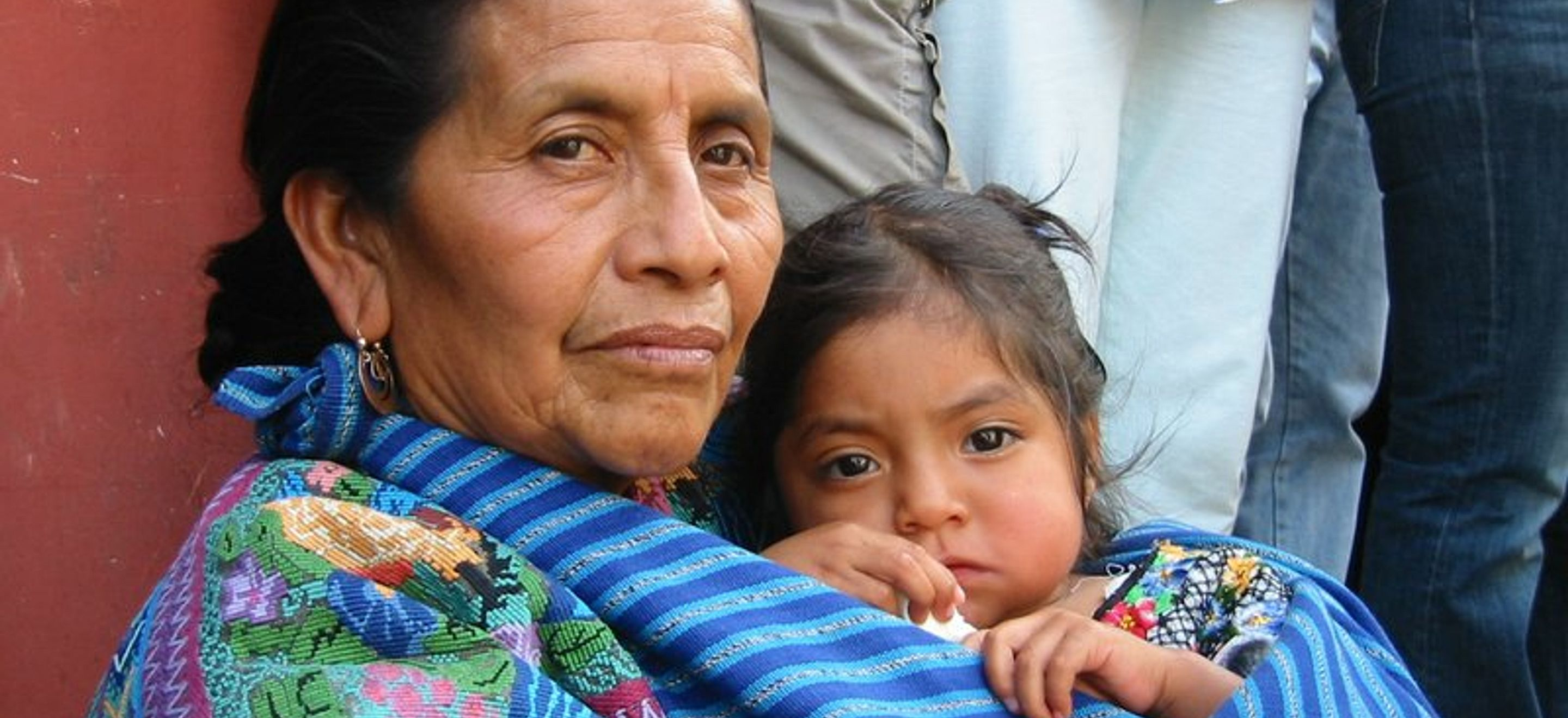 An indigenous Central American woman wearing colorful embroidery has a young girl wrapped to her in embroidered cloth.
